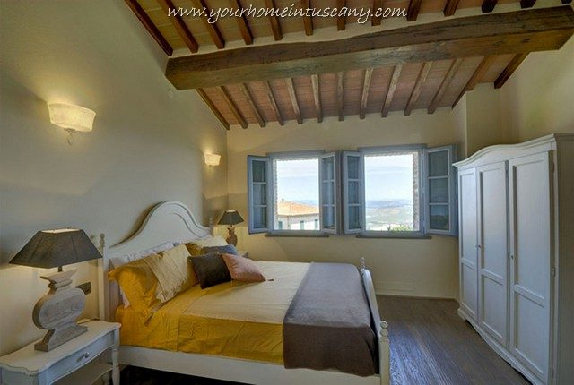 a bedroom with wooden beams