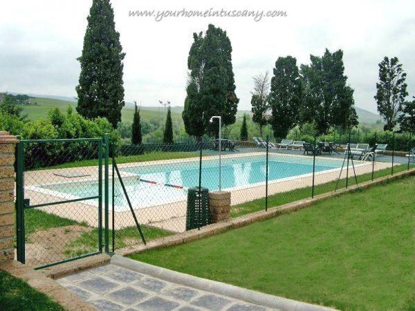 la piscina e i cipressi sullo sfondo
